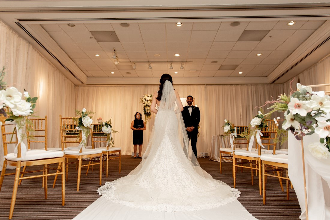 Bride walks down the aisle with train at Vancouver Hilton
