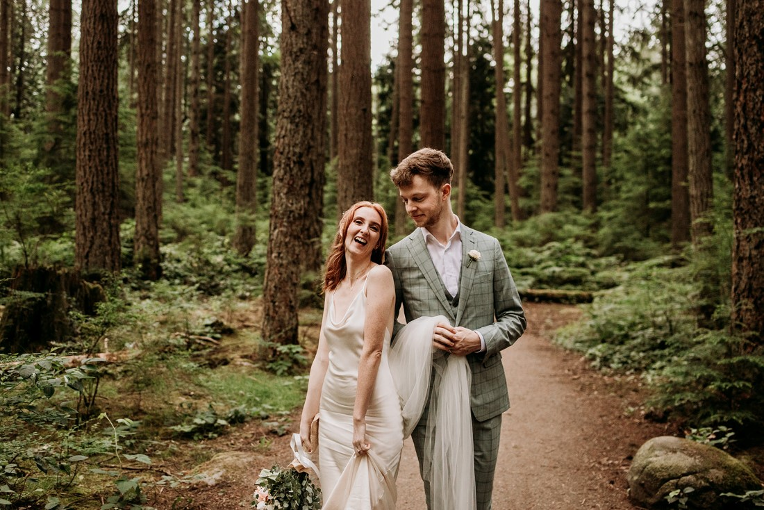 Wedding couple walk along forest path and smile at one another