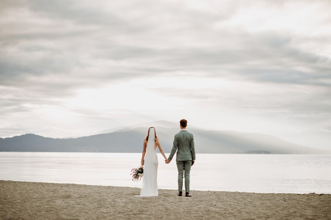 Newlyweds look out at Vancouver mountains with ocean in front of them