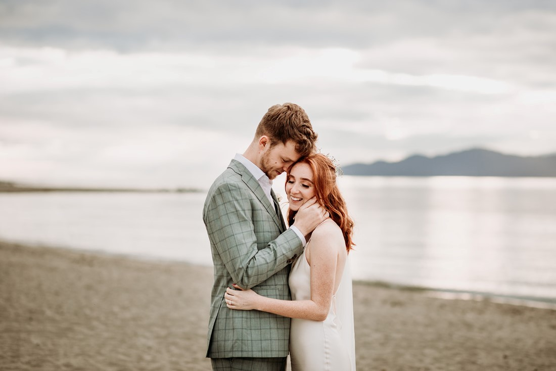 Bride and groom hugging on Vancouver beach