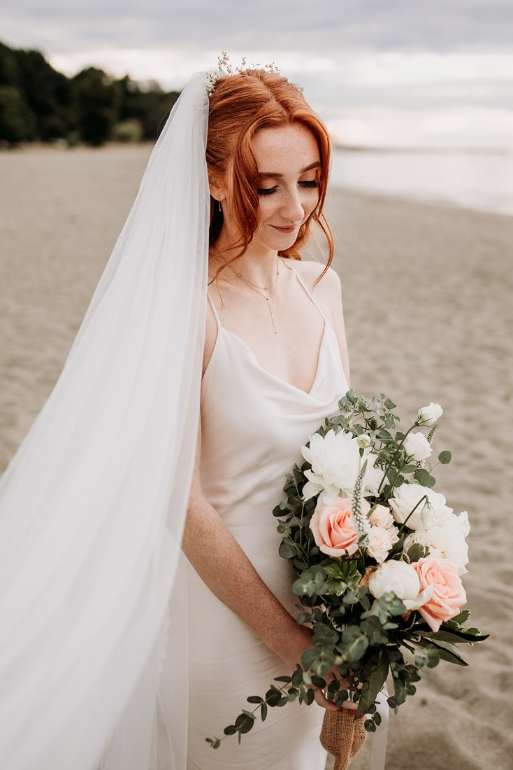 Bride wearing Park and Fifth wedding gown and holding blush and white flower bouquet