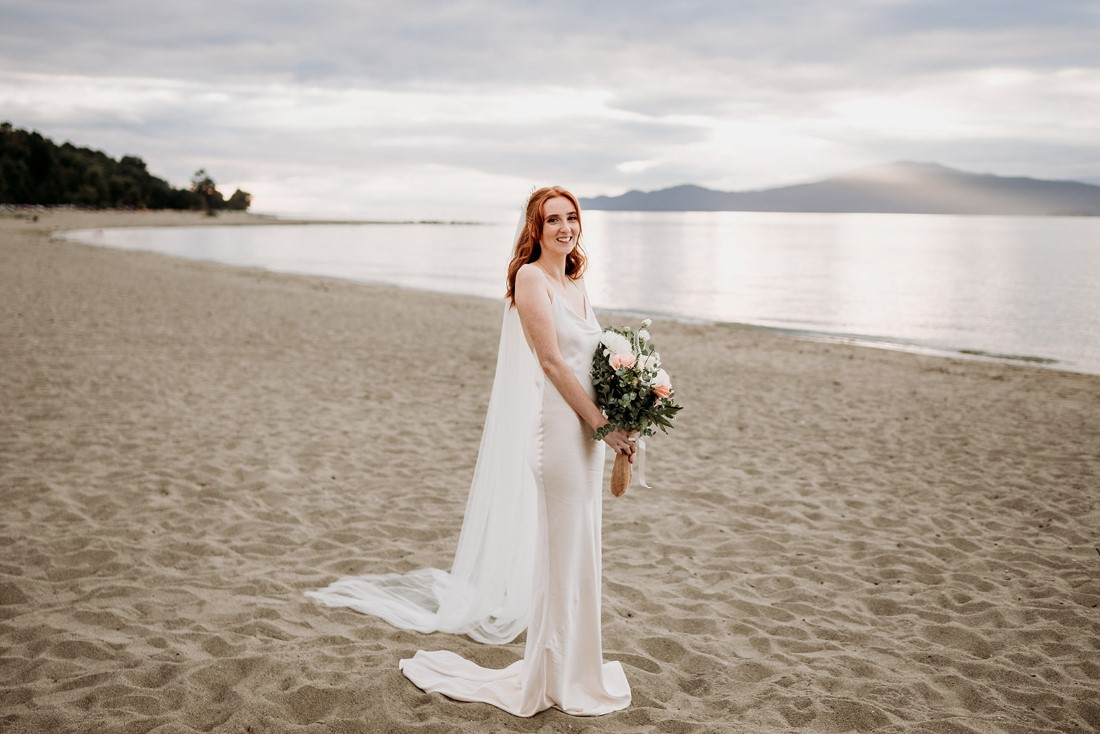 Bride holding bouquet and wearing cathedral veil stands on Vancouver beach
