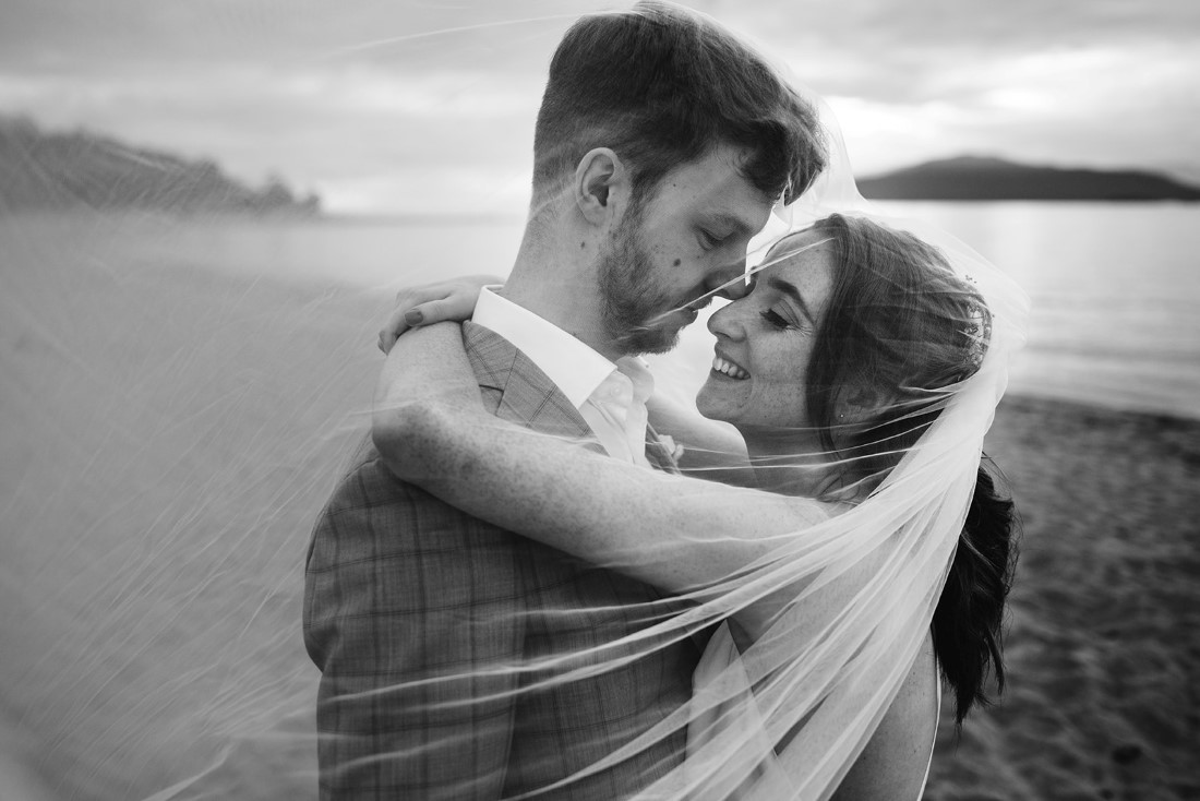 Black and white photo of bride and groom embracing on the beach