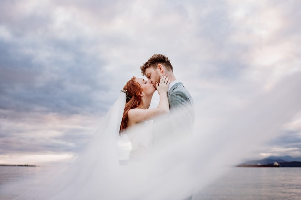 Brides veil swirls around kissing newlyweds with blue sky behind
