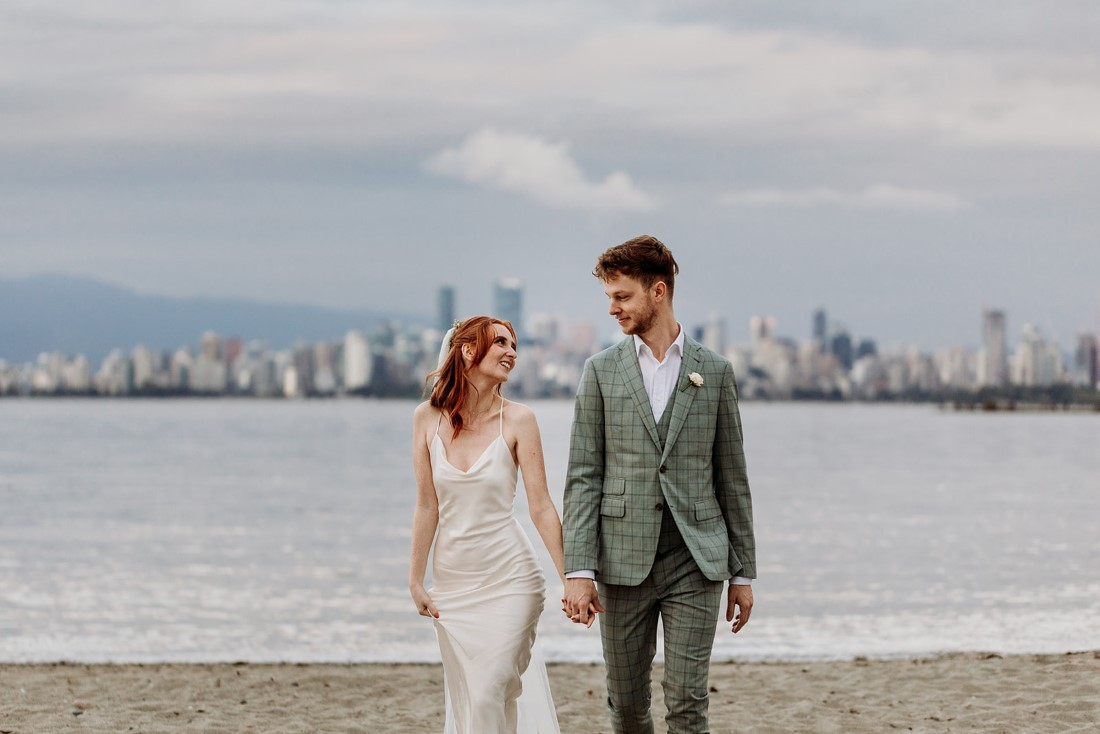 Newlyweds stand in front of Vancouver skyline by Sydney Aleisha Photography