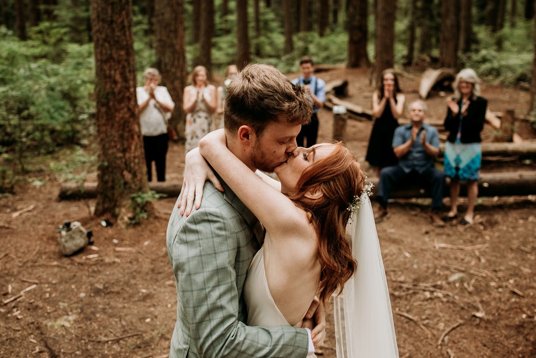 Bride and groom kiss after exchanging wedding vows in the Vancouver Forest