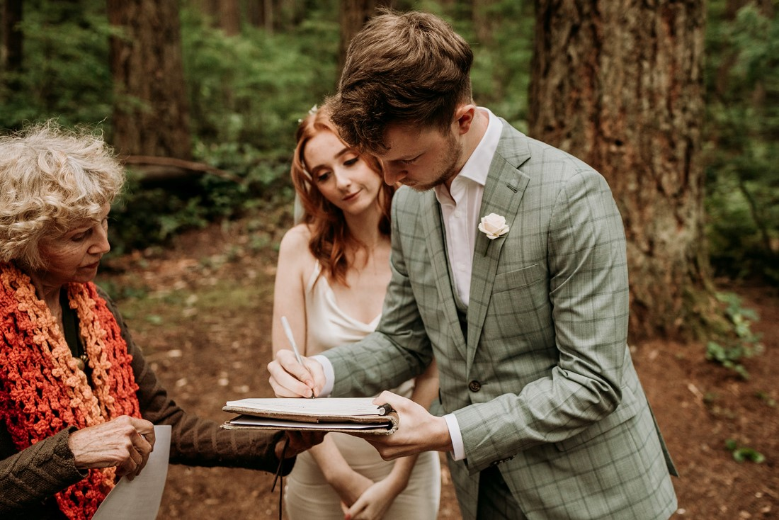 Newlyweds sign register papers in the Vancouver forest