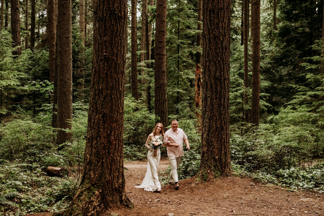Heartfelt Elopement in Vancouver bride is walked through forest path by her father