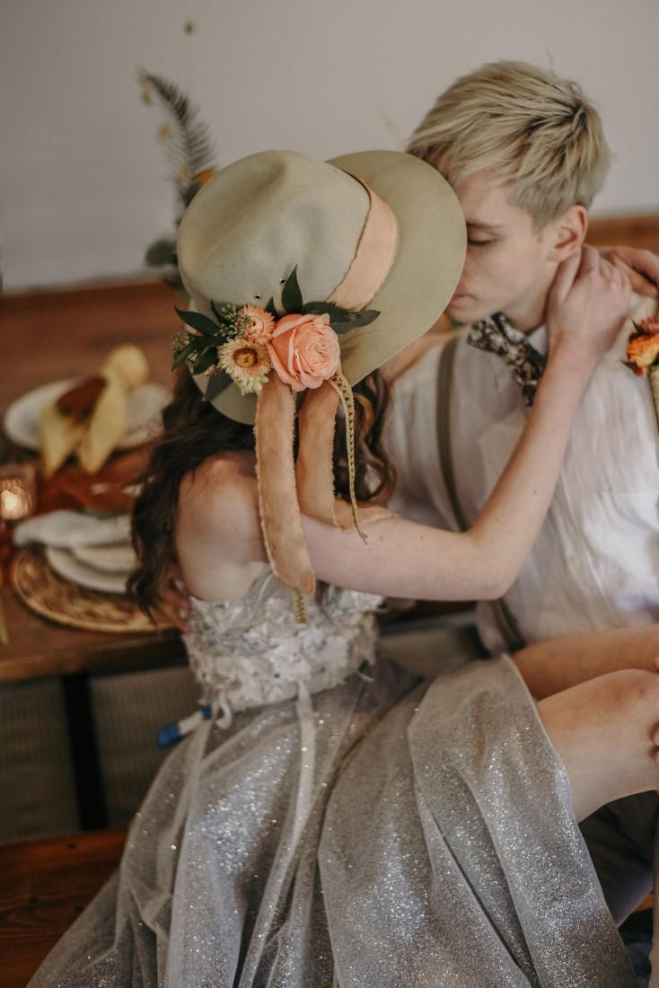 Deep Cove Winery Wedding Dayla Weiss Photo Bride wears bridal hat as she sit across grooms lap