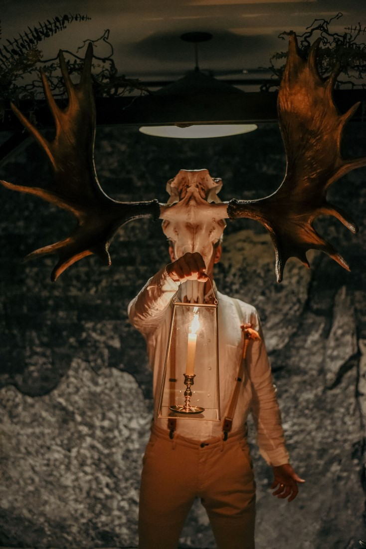 Deep Cove Winery Wedding Dayla Weiss Photo Groom wearing scull with antlers holding a lantern