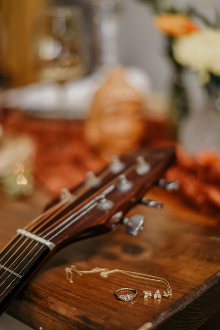 Deep Cove Winery Wedding Dayla Weiss Photo detail shot of jewelry and guitar