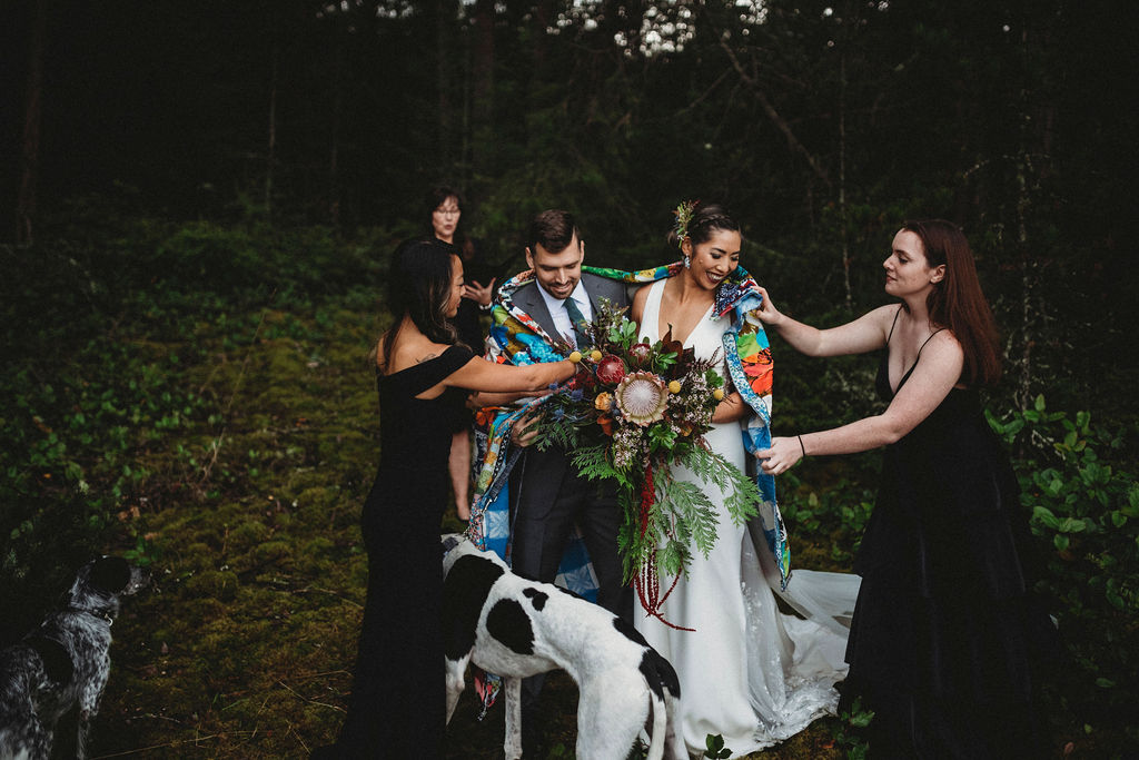 Changing Plans Anastasia Photography bridal party helps put quilt around couple