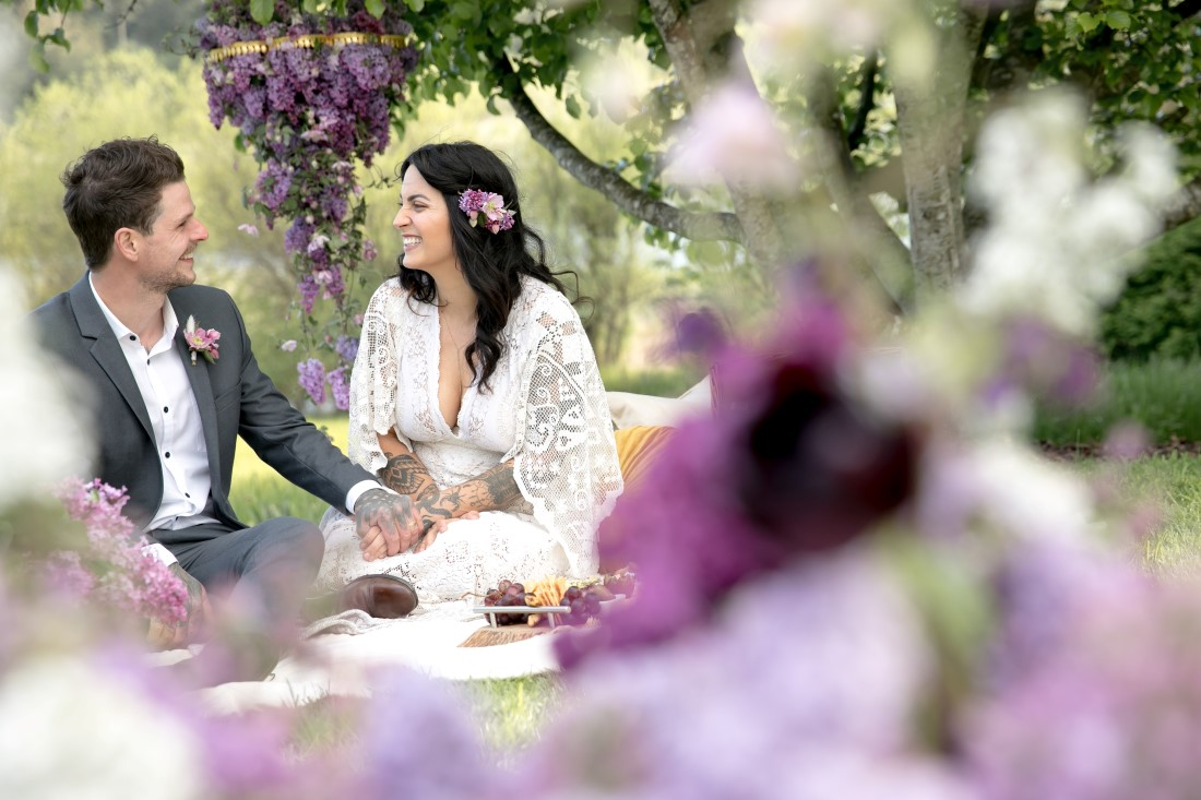 Purple Lilac Spring Wedding Hattie Root Photo Couple share picnic in garden