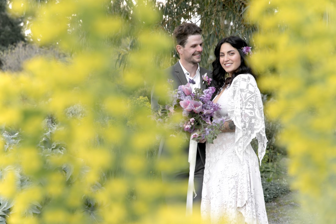 Purple Lilac Spring Wedding Hattie Root Photo groom smiling at his bride in reclamation gown