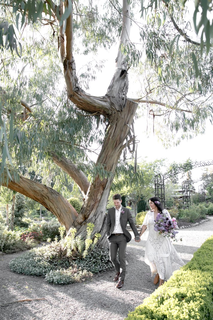 Purple Lilac Spring Wedding Hattie Root Photo bride and groom walk handing in hand