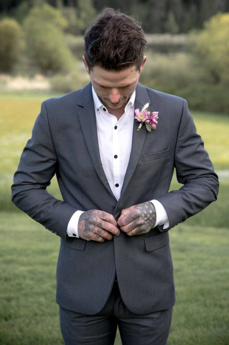 Purple Lilac Spring Wedding Hattie Root Photo groom buttoning up his suit jacket