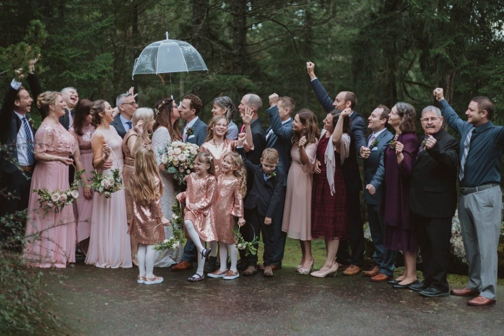 Sophisticated Gallery Kacie McColm Photography kissing under umbrella with wedding party