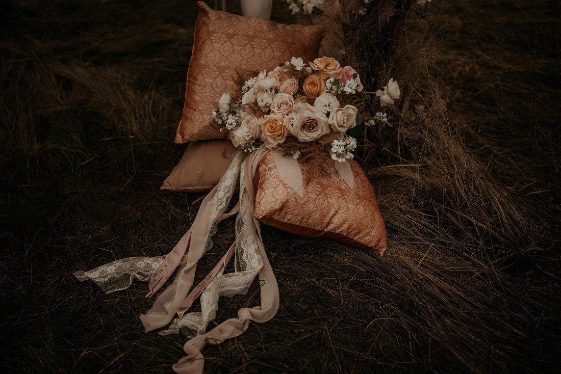 Romantic Cover for Vancouver Island Magazine Secret Waters Photography bridal bouquet with lace and ribbon tails lays on decorative pillows