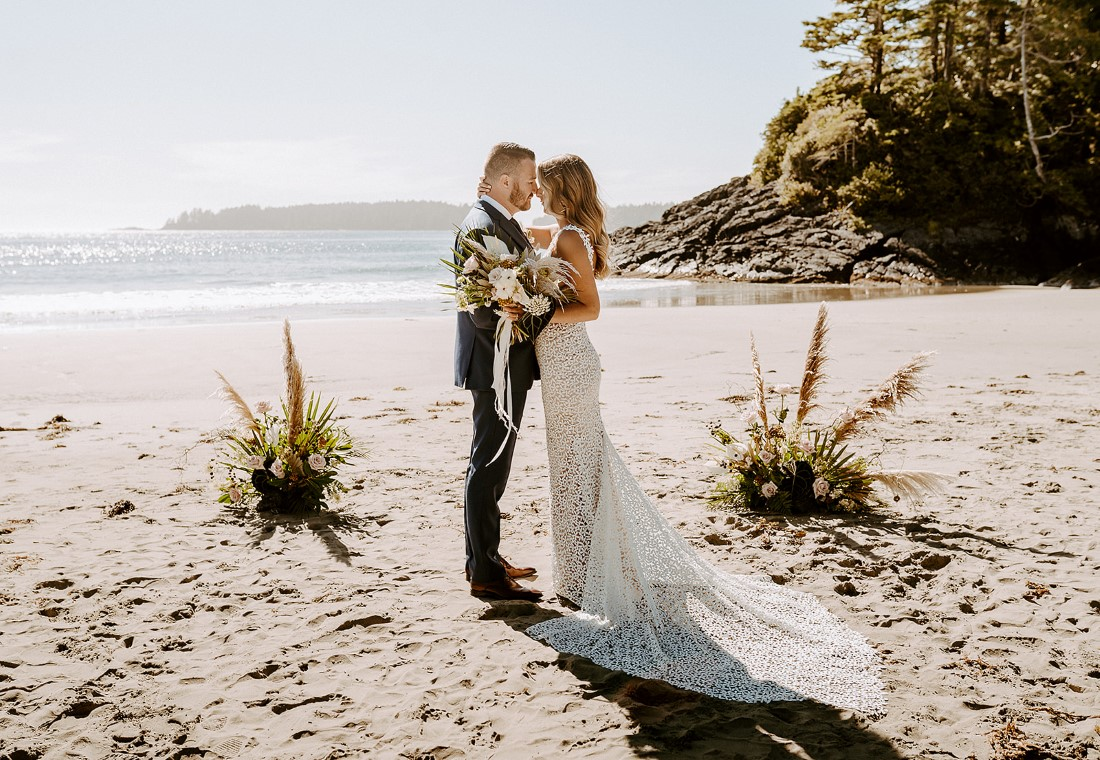 Beach Wed in Tofino couple stand between floral arrangements Crab Appl;e Floral