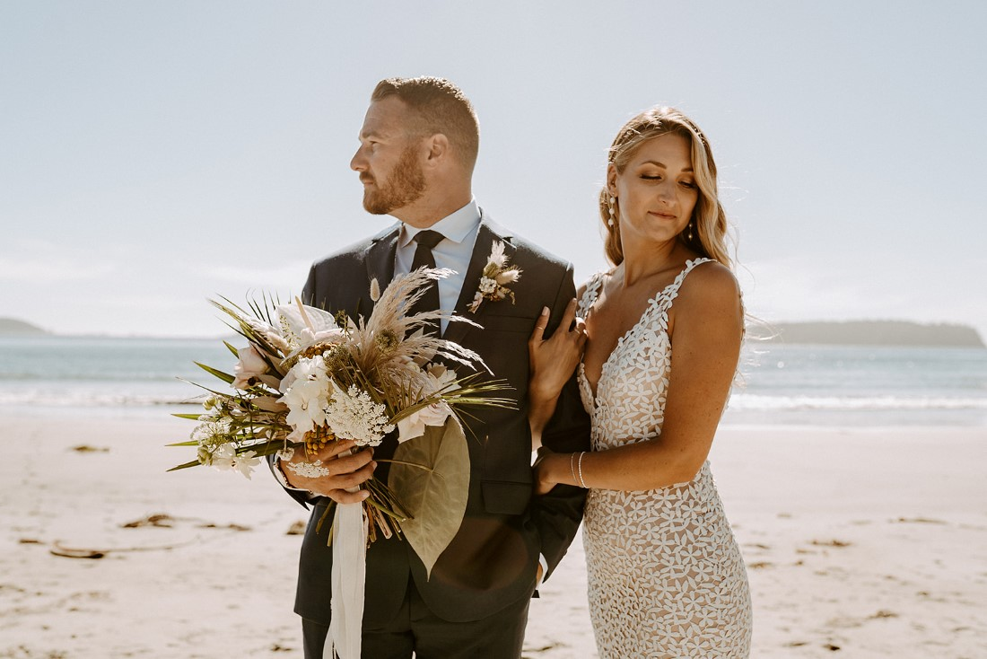 Groom holds Crab Apple Floral bouquet as bride holds on to his arm on Tofino beach