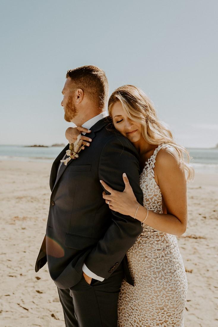 Bride leans her head against grooms shoulder on Tofino beach