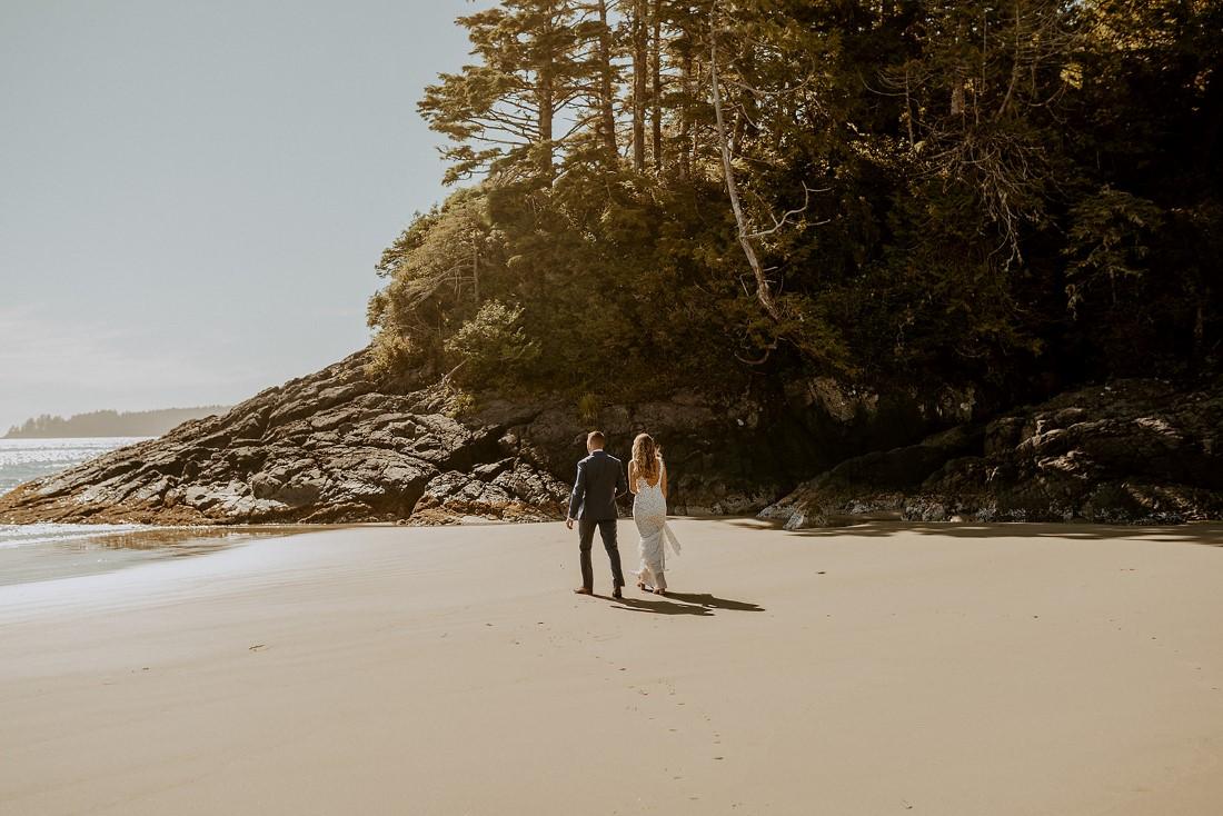 Newlyweds in Tofino walk along ocean edge