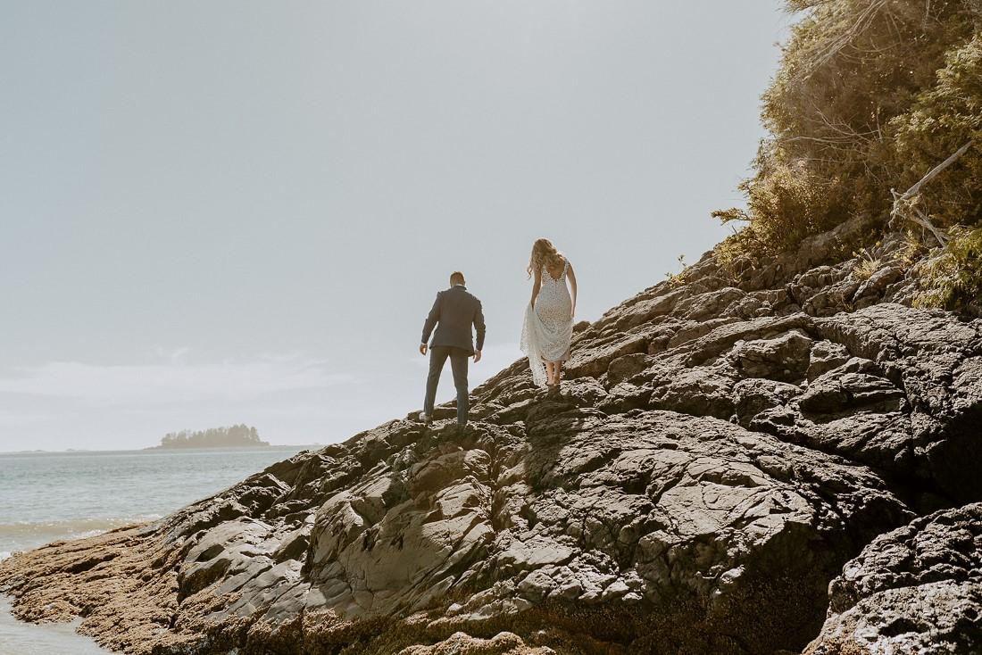 Adventurous eloping couple climb up rock face of cliff on Tofino beach
