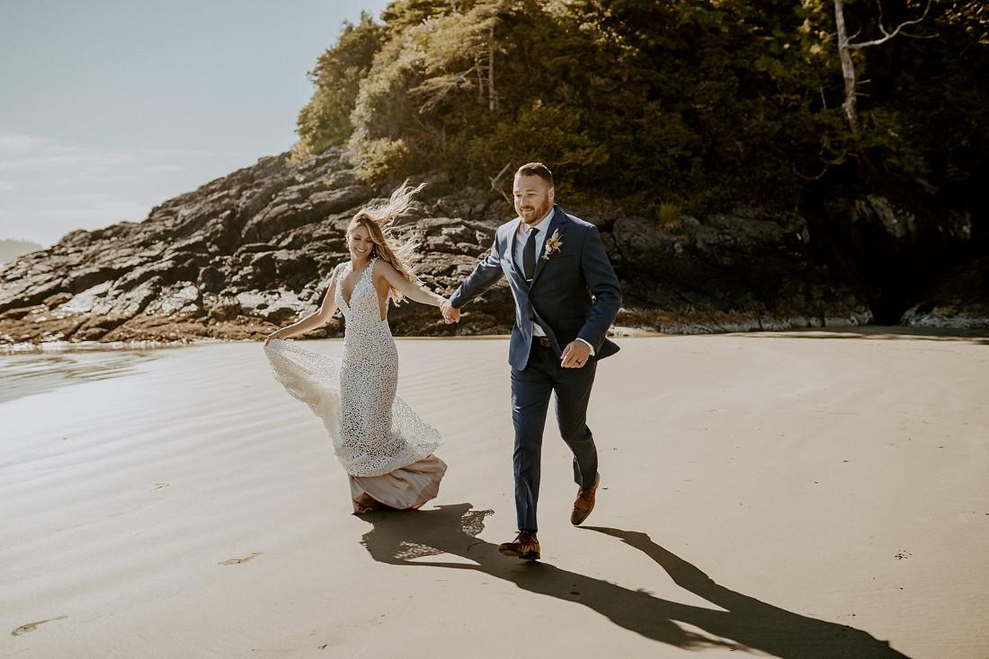 Newlyweds holding hands and running along Tofino beach