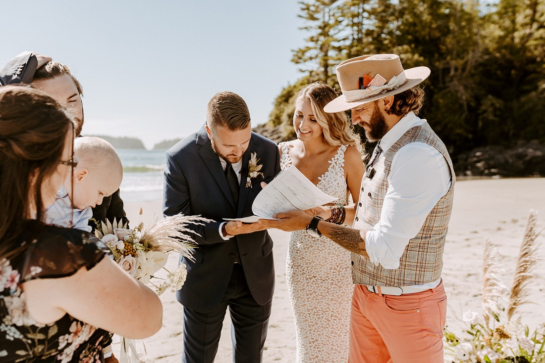 Couple exchange rings during beach wedding in Tofino