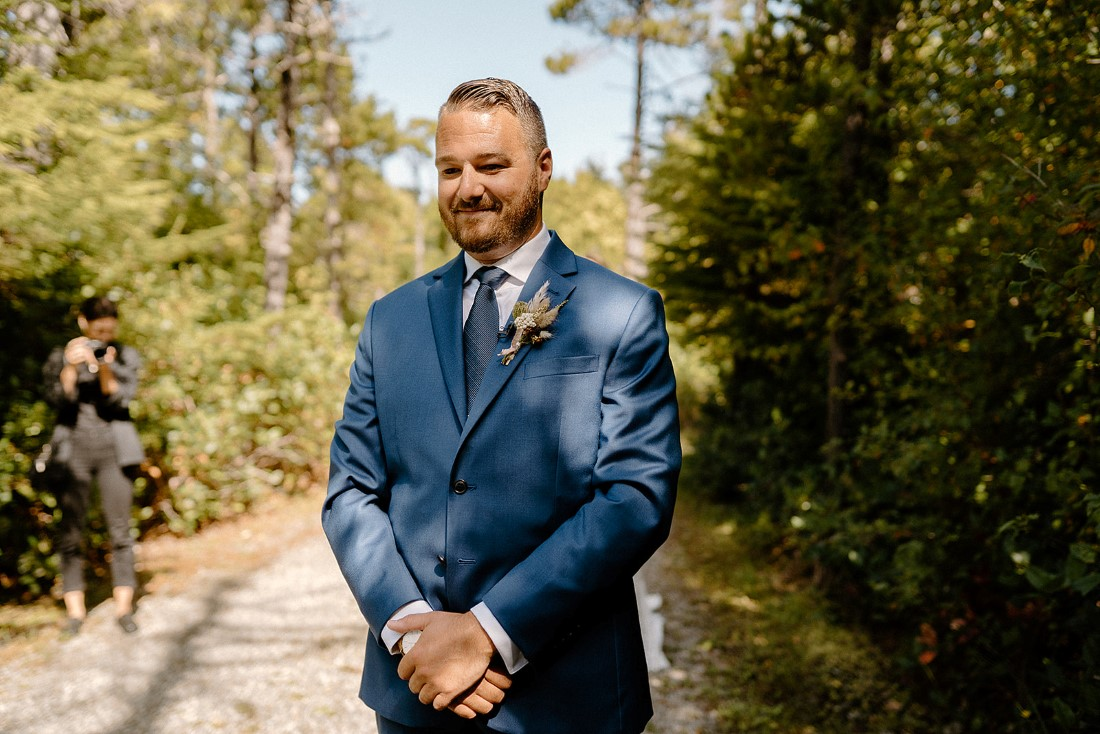 Groom in blue suit smiles at camera on path in Tofino