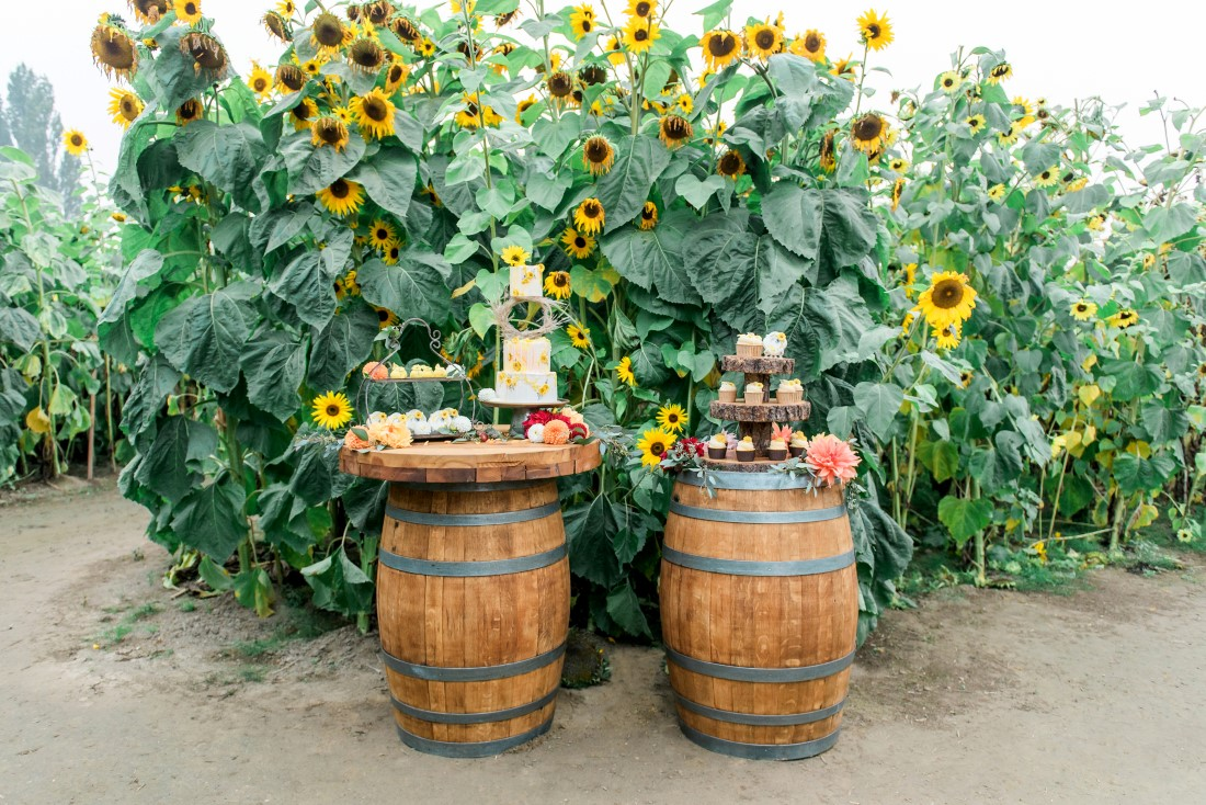 Sunflowers and Sunshine Wedding Inspo dessert table showcased on barrels