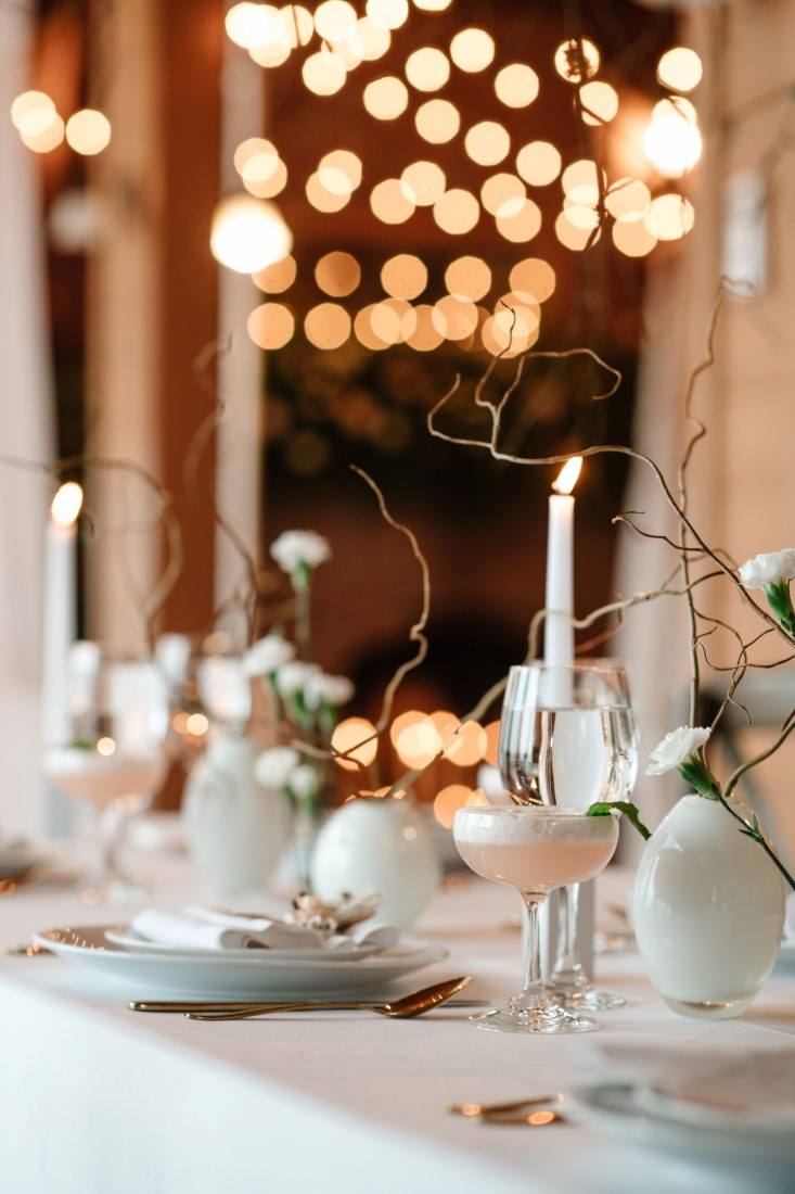 White taper candles on white linens at wedding reception table by Bezaire Events