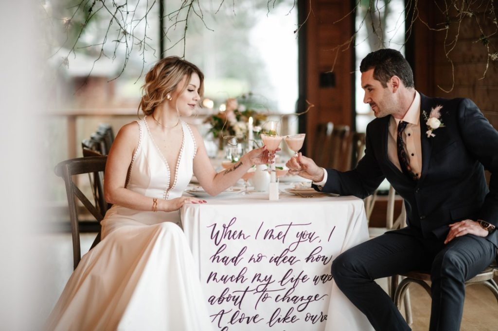 Love Letters at Dolphin's Resort newlyweds drink champagne in front of calligraphy linen