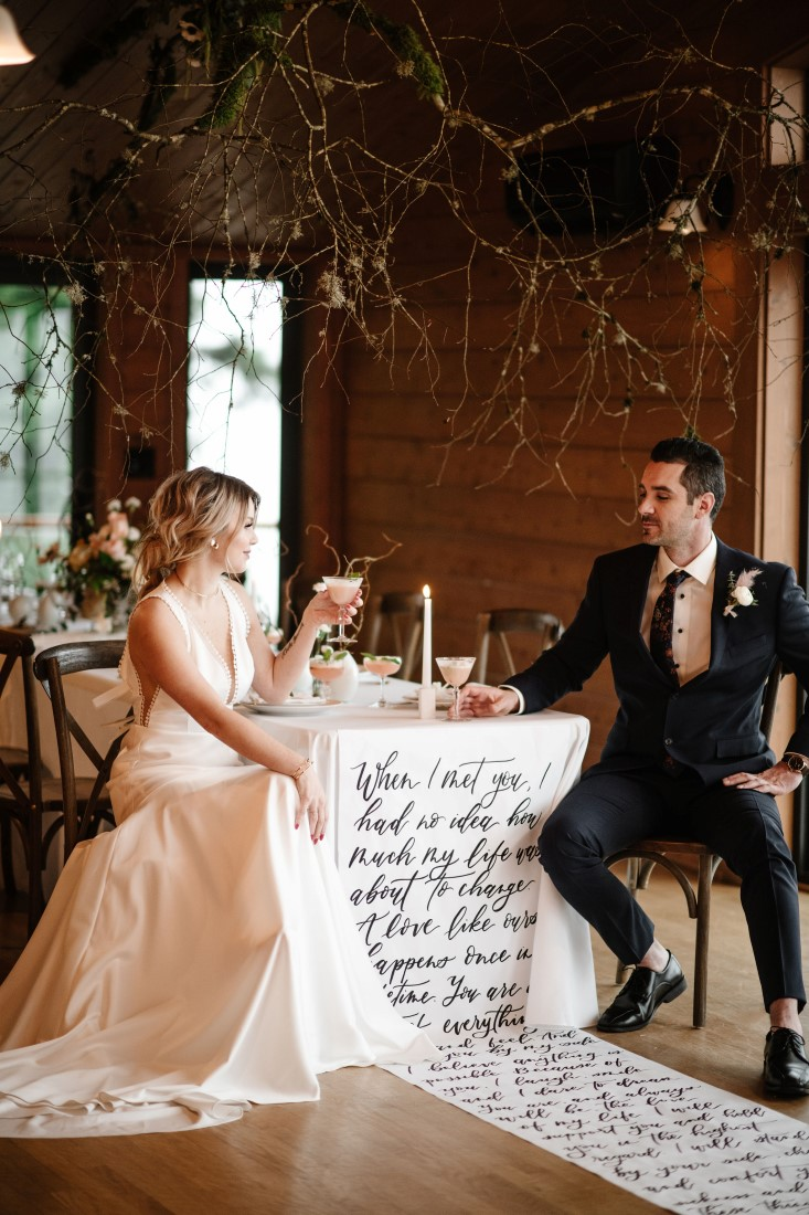 Bride and Groom sit at reception table with calligraphy linen at Dolphin's Resort