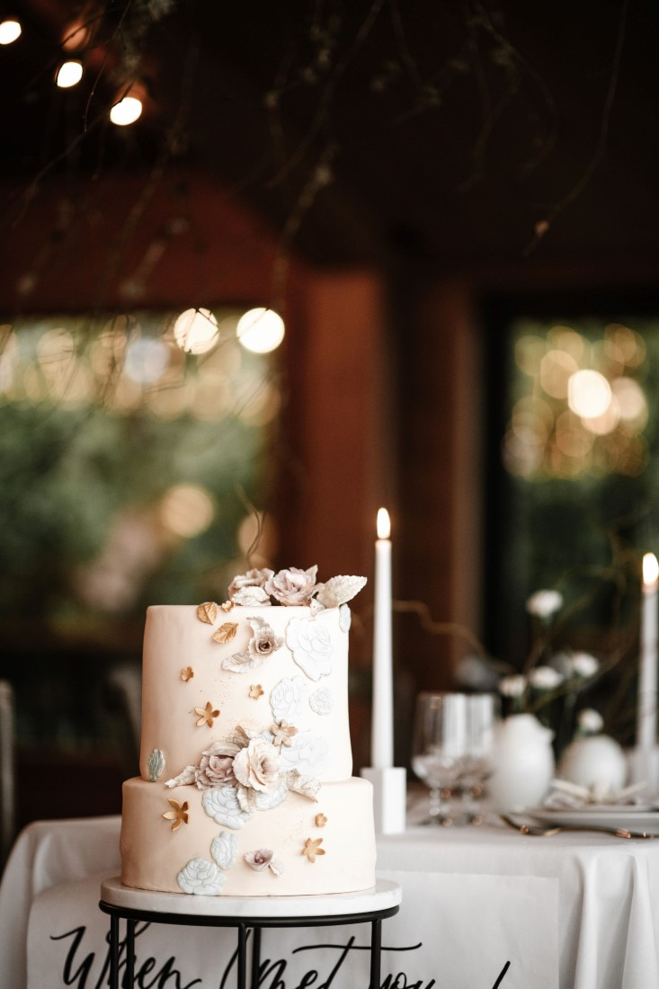 Wedding Cake by Cakebread Artisan with white icing and tall white candle at Dolphin's Resort
