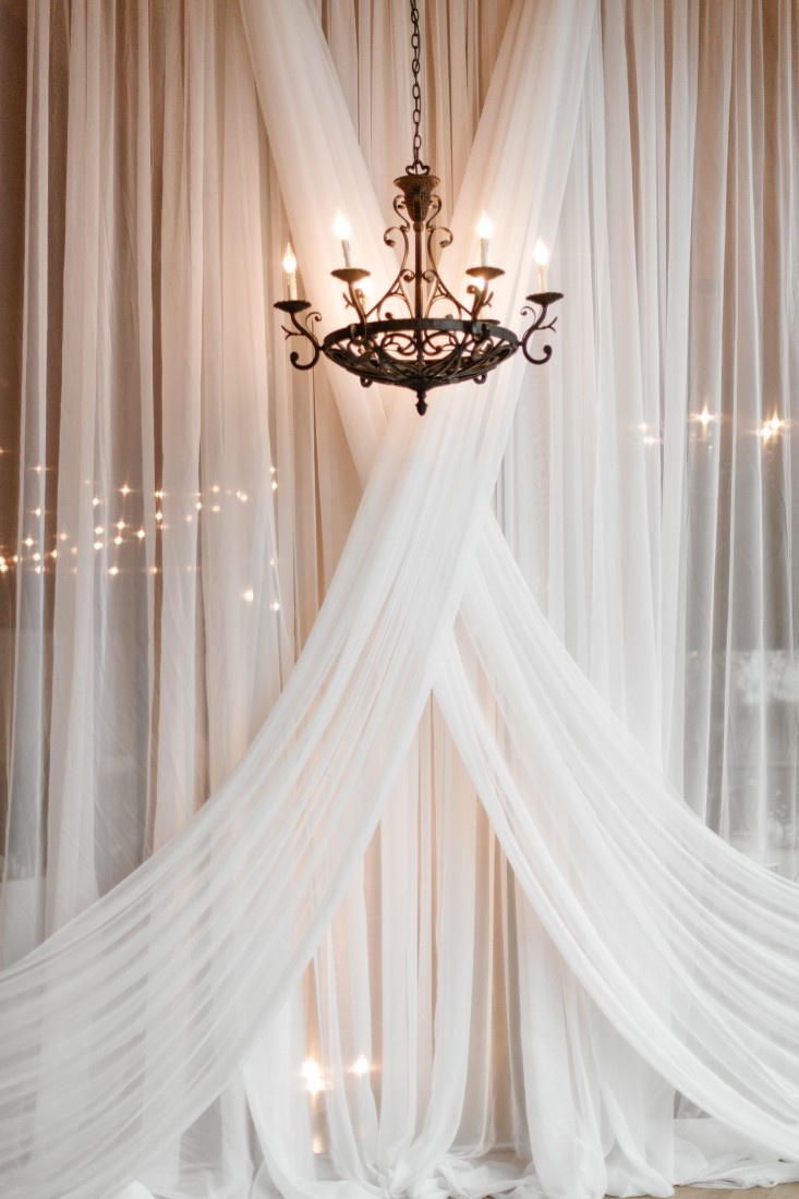Love Letters White Drapery with Chandelier backdrop for wedding at Dolphin's Resort