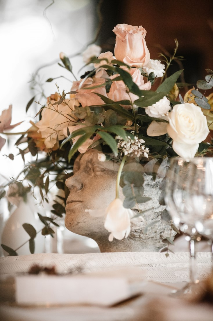 Blush flowers inside sculpture vase on wedding reception table by Erin Wallis Photography