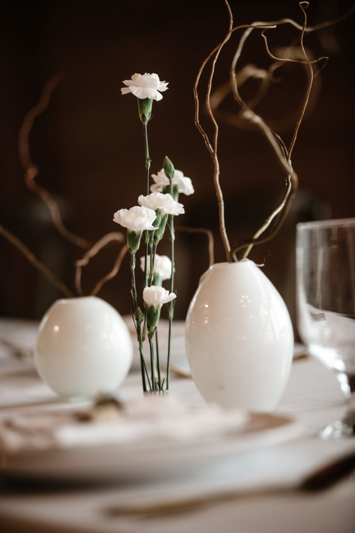 White modern vases hold twigs and flowers on wedding reception table at Dolphin's Resort