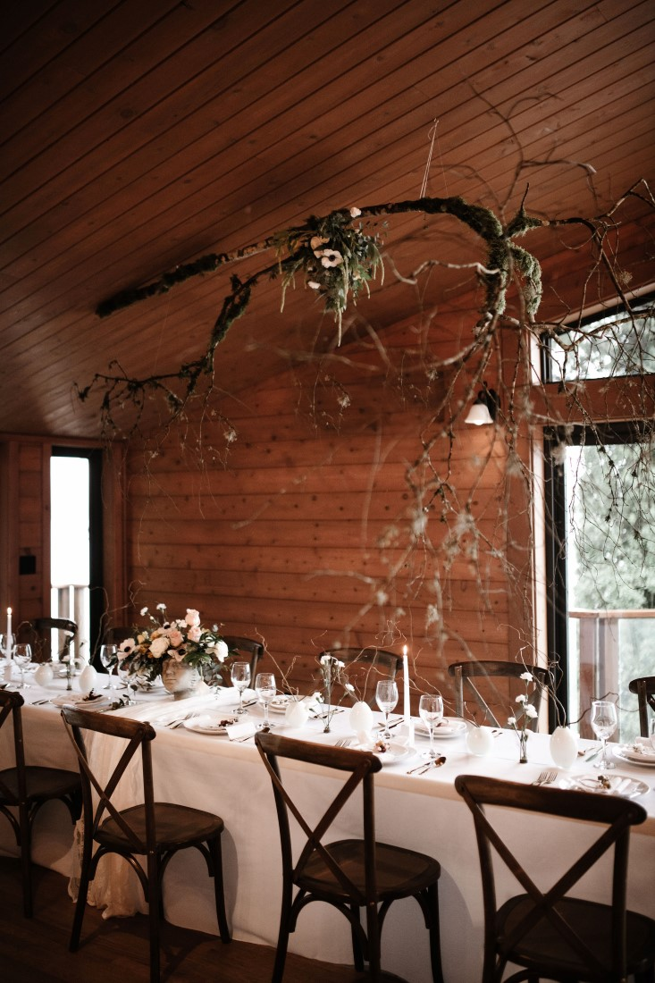 Twigs and flowers hung above wedding reception table by Bezaire Events