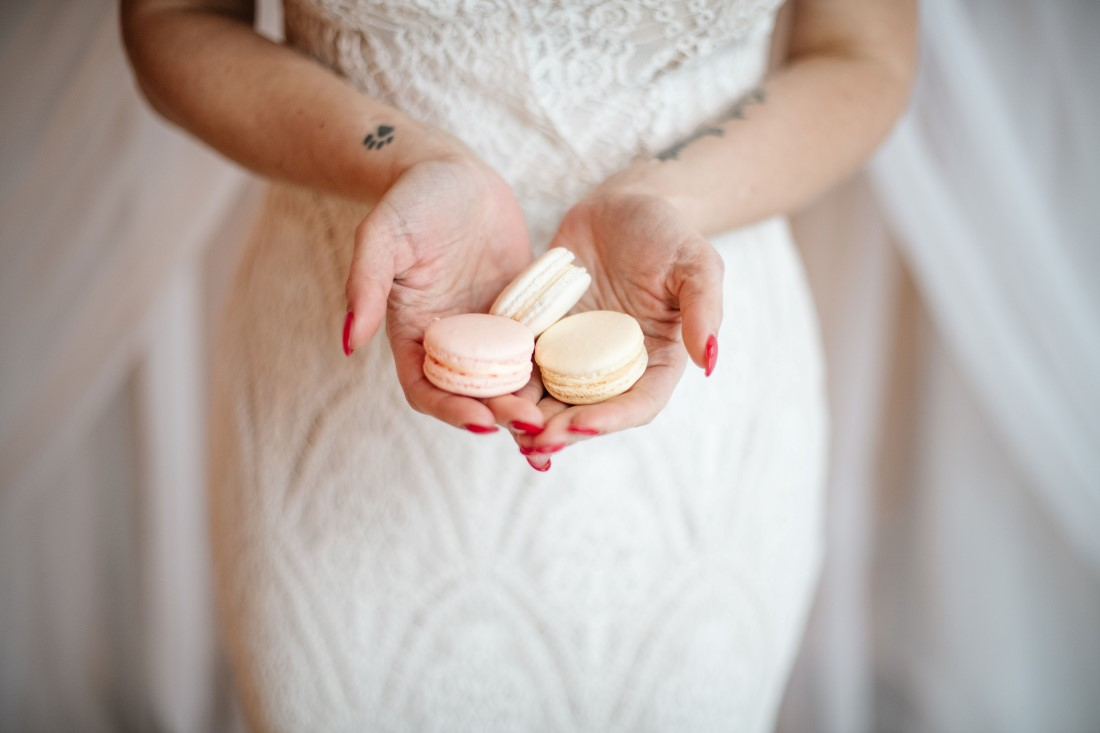 Bride holds blush pink macarons in her hand by OMG Macarons