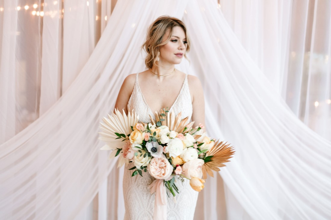 Unbridled Courtney bride stands in front of white drapery holding pastel bouquet