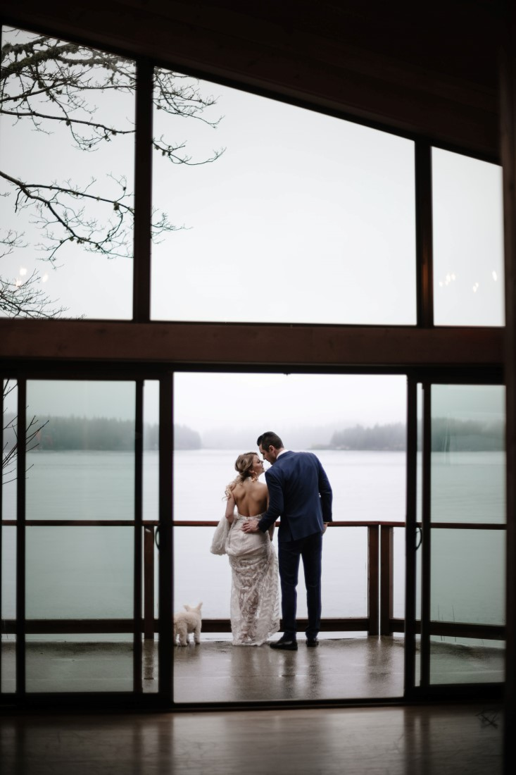 Newlyweds look at ocean through wall of windows at Dolphin's Resort by Erin Wallis Photography