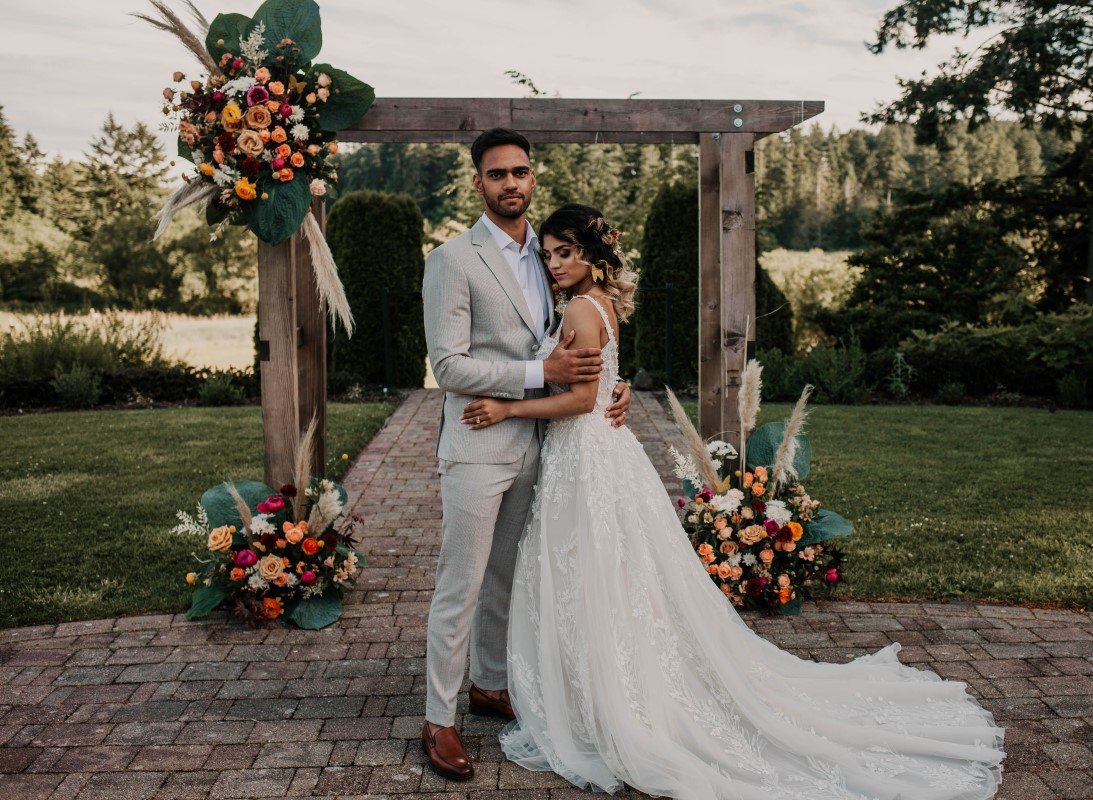 Newlyweds in front of ceremondy backdrop at HCP Gardens by Kelsey Lageri Photography