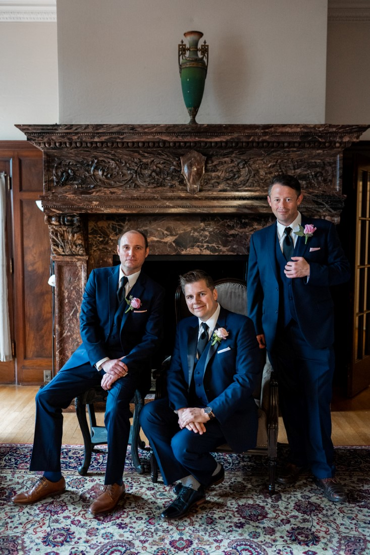 Groomsman photo in front of fireplace at Hycroft Manor by Justin Kho Photography