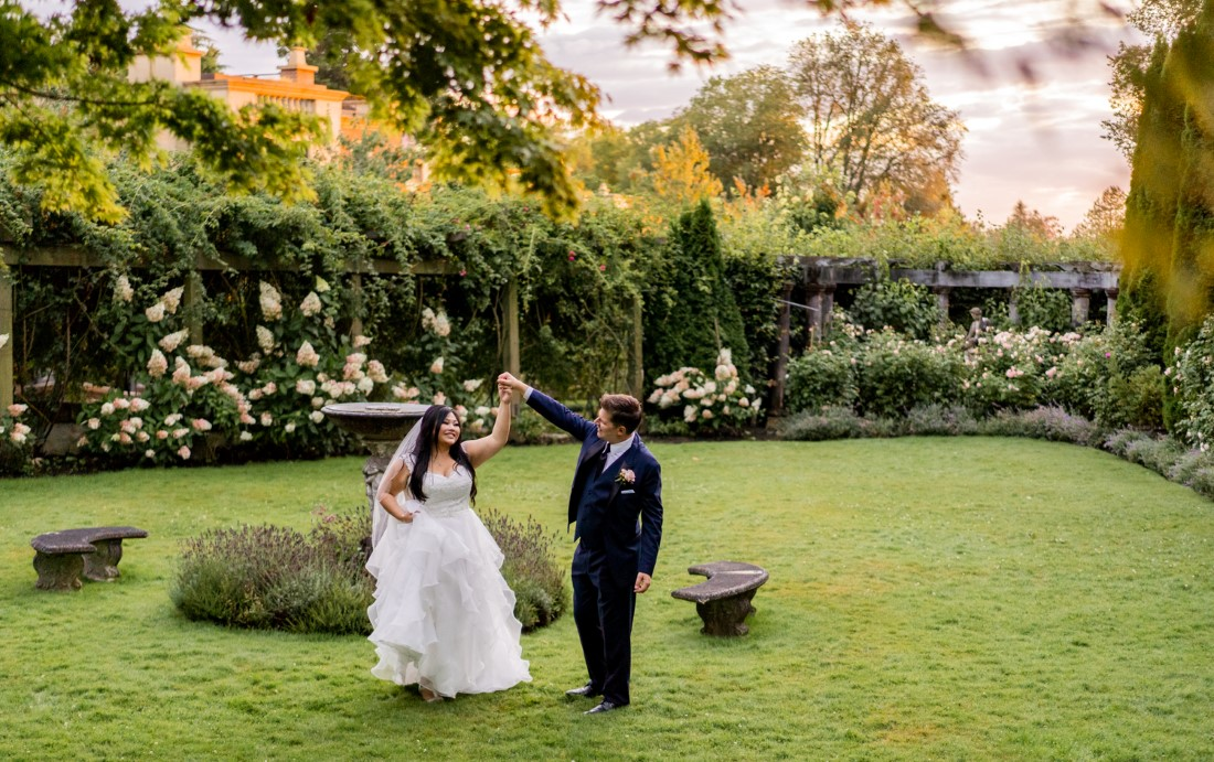 Newlyweds dance in the Rose Garden at Hycroft Manor at UBC
