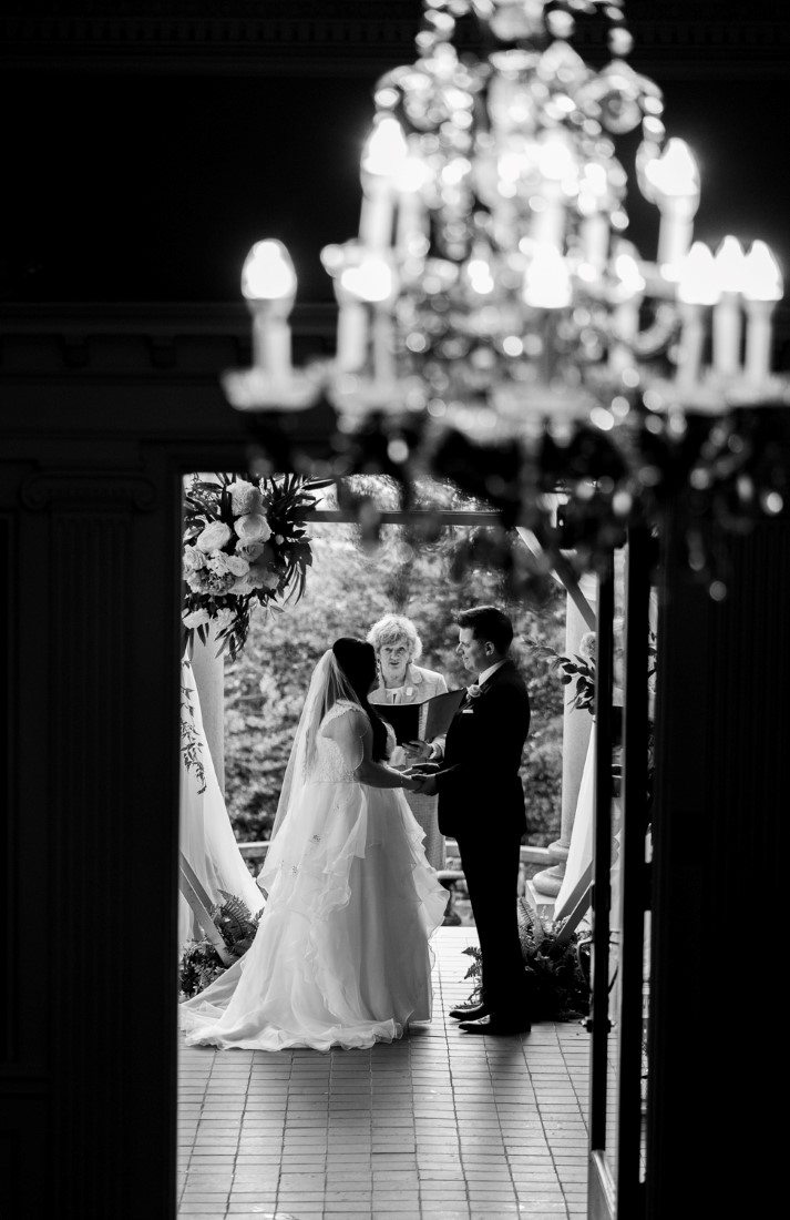Newlyweds stand in the door framed by chandelier at Hycroft Manor Vancouver by Justin Kho Photography