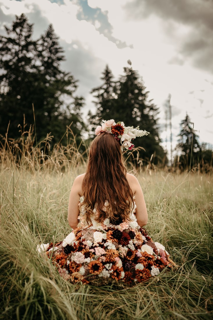 Flirty Floral Gown bride runs through field of flowers on Vancouver Island