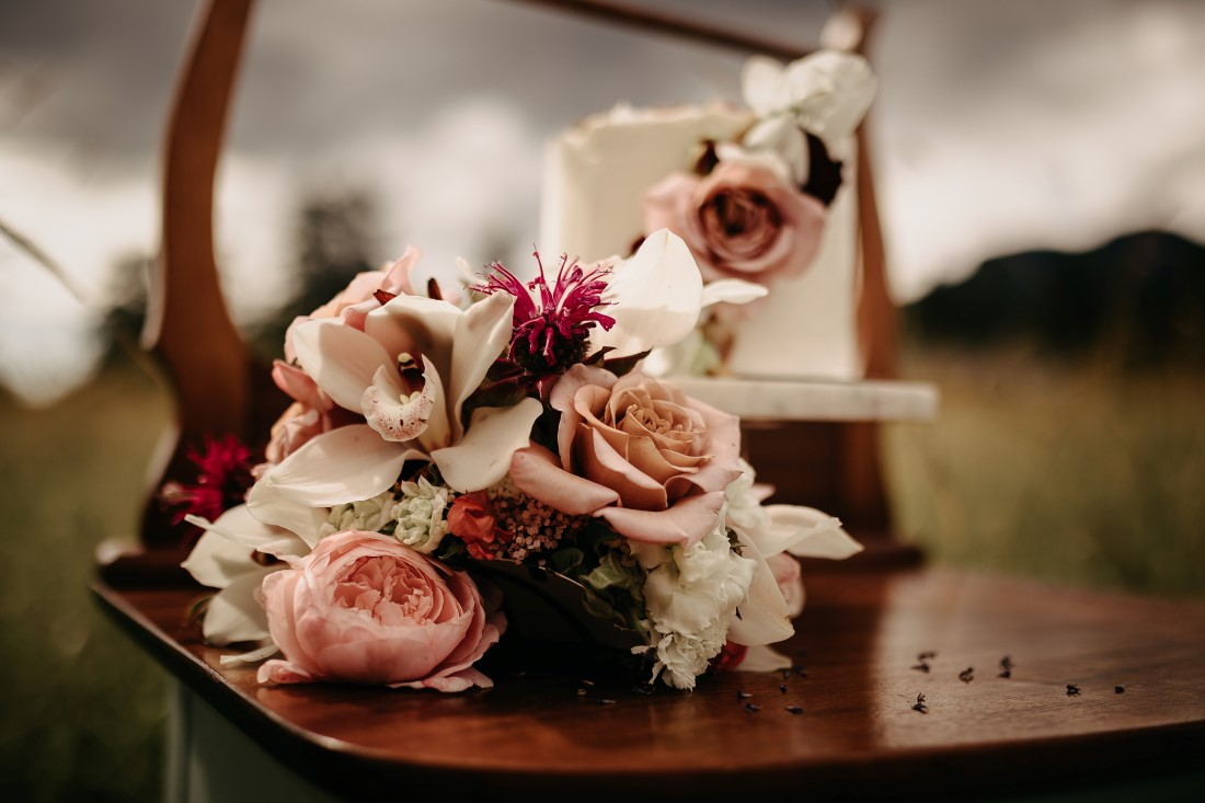 Wedding Cakes sit on vintage dresser in field of flowers on Vancouver Island