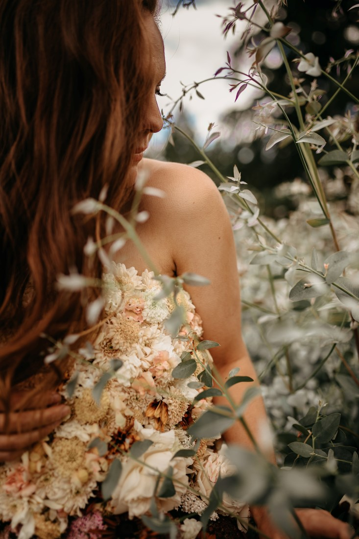Flirty Floral Gown bride runds through meadow of flowers on Vancouver Island