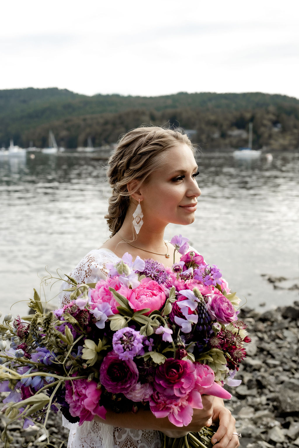 Bride holds pink and purple bouquet beside ocean edge by Little Bee Blooms Vancouver Island